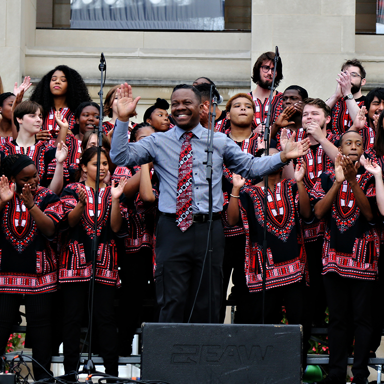 The African American Choral Ensemble performing outdoors on an IU stage