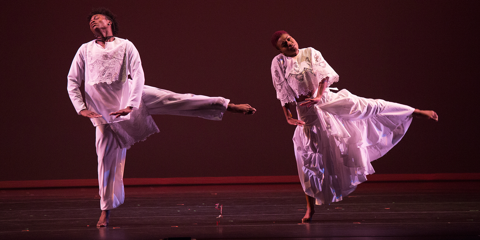 Two performers dance a duet onstage